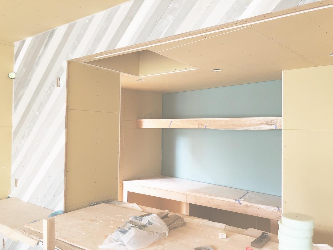 グレーとホワイトを混ぜ合わせながらランダムに塗った板壁。背面収納部分は未来建築工房のテーマカラーでもあるブルーグレーで塗装。